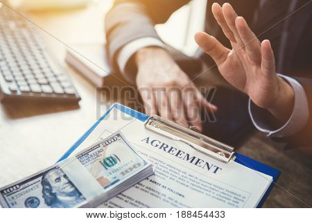 Businessman refusing money that come with agreement paper - anti bribery and corruption concepts