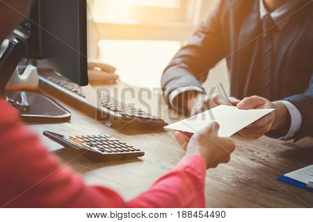 Businessman receiving envelope (money) from a woman at working desk - bribery concept