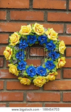 Blue yellow memory wreath on old wall