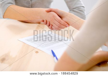 Young business woman shaking hands after signing contract.