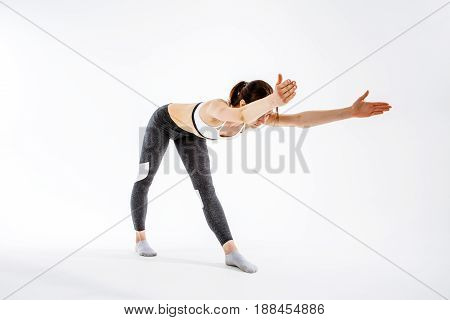 Sporty girl engaged in gymnastics on blank background
