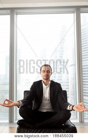 Businessman meditating on coach with crossed legs. Entrepreneur relaxing in lotus position, concentrates on positive thoughts, struggling with stress. Man doing yoga exercises near window, copy space