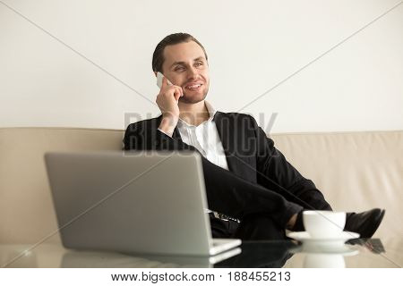 Young businessman talking on phone during coffee break in office. Relaxed entrepreneur sitting on sofa in front of laptop and answers the call. Successful company leader work remotely from hotel room