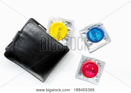 condoms and wallet for male contraception and birth control on white background top view