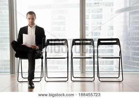 Confident job applicant reads resume while sitting on chair in row in office and waiting his turn on interview. Young guy wearing suit prepares for recruitment meeting with employer in waiting room