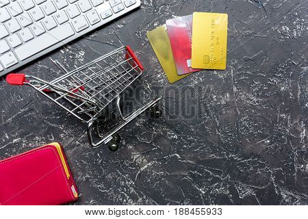 buying products with credit cards and mini trolley on dark table background top view space for text