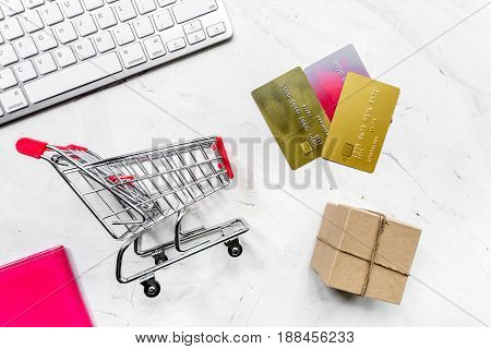 office desk with mini trolley and cards for online buying on light background top view