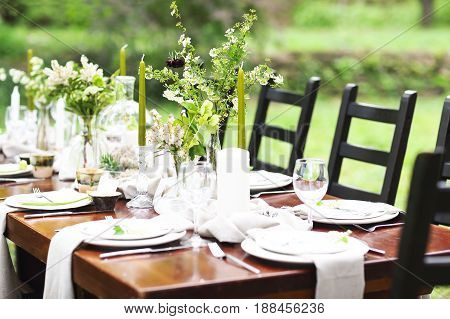 Decoration of wedding table with crystal vases flowers and branches in botanical style