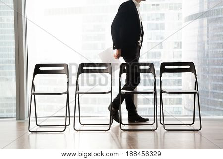 Man in business suit passing by row of chairs in reception. Office worker walking in waiting room while waiting important meeting with boss. Places for guests, job applicants and candidates on post