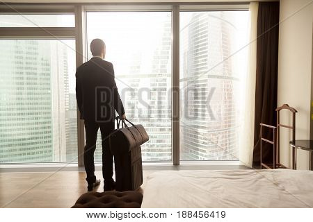 Man in business suit standing with suitcase and handbag in luxury hotel room, looking on modern cityscape outside window. Businessman with luggage thinking about business trip or vacation, back view