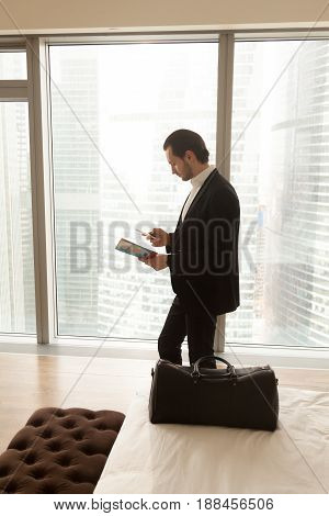 Man in business suit with travel guide or brochure in hand calls taxi from hotel room, orders dinner in apartment using phone, buys airline tickets via cellphone mobile app. Business trip or vacation