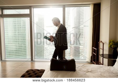 Businessman with luggage calls taxi from luxury hotel room. Tourist reading guidebook, booklet in search of tourist attractions. Traveler orders food dialing cellphone number from hotel telephone book