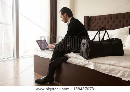 Real estate agent examines house drawing on laptop screen before travel flight. Businessman tenant arrived in hotel with luggage and working on laptop. Guy checks presentation for meeting with partner