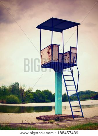 An Old White And Rusty Metal Lifeguard Tower With Chair On A Lake Beach.