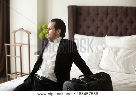 Man in business suit sitting on hotel room bed with luggage, relaxing, looking in window. Successful businessman ready to business trip abroad, dreaming about weekend leisure, foreign country vacation