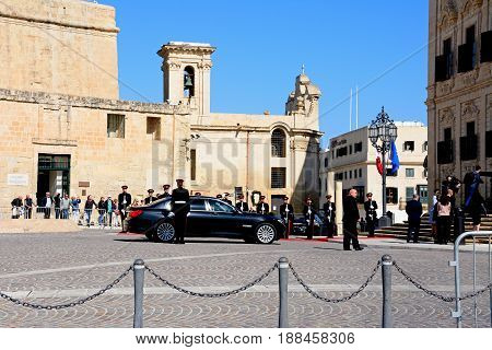 VALLETTA, MALTA - MARCH 30, 2017 - Politicians arriving in a limousine at the Auberge de Castille for a European Union conference with soldiers on parade in Castille Square Valletta Malta Europe, March 30, 2017.