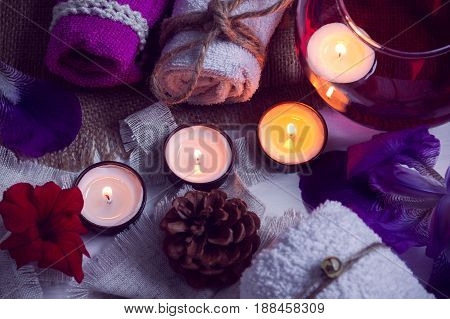 SPA consist from towels, candles, flowers, cone and aromatherapy water in a glass bowl on a white wooden background