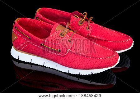 red leather moccasins on a black background, isolated