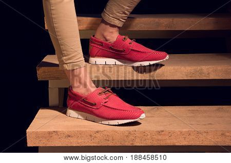 legs with a red leather moccasins on a wooden stairs