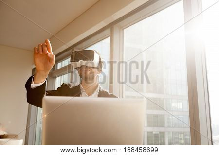Businessman working in office with virtual reality glasses on head. Man using VR headset for editing project or document in augmented reality. Entrepreneur interacts with three-dimensional simulation
