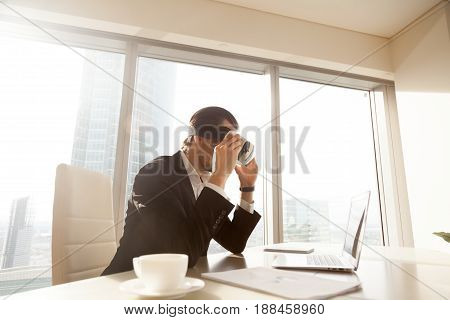 Businessman synchronizes VR headset with applications on computer. Office worker looking at laptop screen through virtual reality glasses. Man using digital goggles while sitting at desk in office