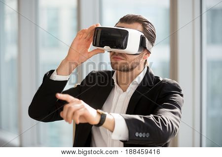Businessman using technology of augmented reality in daily office work. Man ceo wearing virtual reality glasses, pointing at the air. Office worker in electronics 3d goggles interacts with simulation