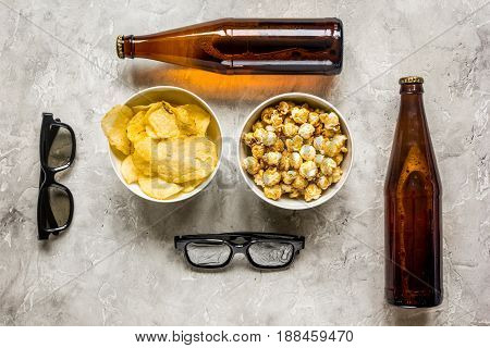 film whatching party with beer, chips and pop corn on stone background top view