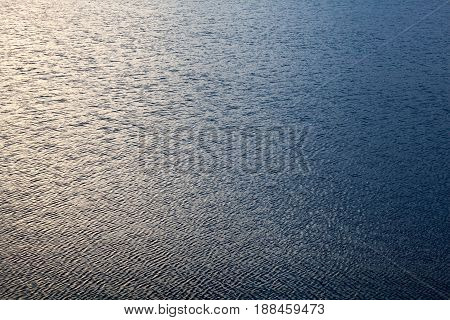 Water surface with ripples. Windy weather. Background or texture.