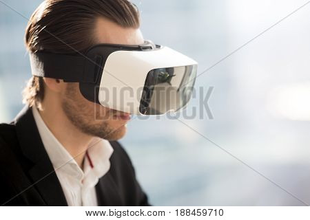 Close up photo of virtual reality glasses on mans head. Businessman looking in VR headset. Work in augmented reality, digital entertainments, virtual gaming, cyberspace experience concepts. Copy space