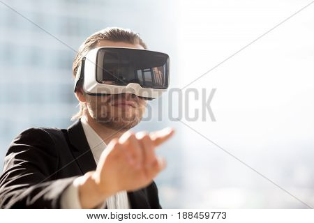 Businessman pointing in air in virtual reality glasses on head. Man in VR headset using gestures in app virtual interface. Male entrepreneur editing project in augmented reality, portrait. Copy space