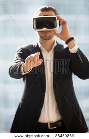Businessman wearing virtual reality glasses, touching objects in digital world. Man in VR headset choosing, operating in virtual interface. Entrepreneur using electronic goggles for 3d visualization
