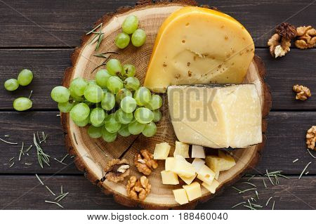 Cheese platter, gouda herb on natural wood disc with grapes and nuts, still life, top view