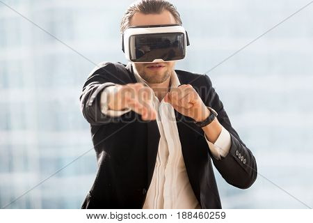 Man in business suit boxing with virtual reality glasses on head. Guy playing computer fighting game in VR headset. Digital entertainments, new technology, innovations in modern game industry concept