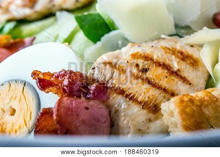 Salad. Salad Ceasar. Ceasar salad with quail egg lettuce bacon crutons and grill chickens breast.