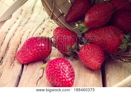 red strawberries rolled out from a basket on a wooden background