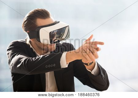 Businessman in VR headset with gun from fingers playing in shooter computer game. Man in suit wearing virtual reality glasses and aiming with finger gun in game simulation. Digital entertainments