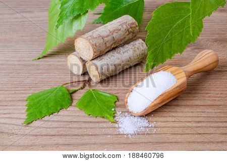 sugar substitute xylitol, a scoop with birch sugar, liefs and wood on wooden background