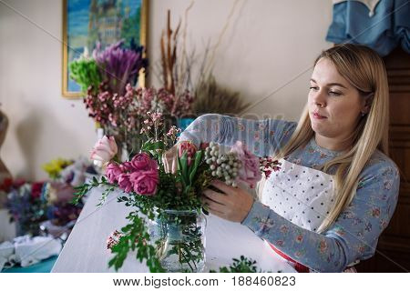 woman florist making bouquet of flowers indoor. Female florist preparing bouquet with roses peony in flower shop