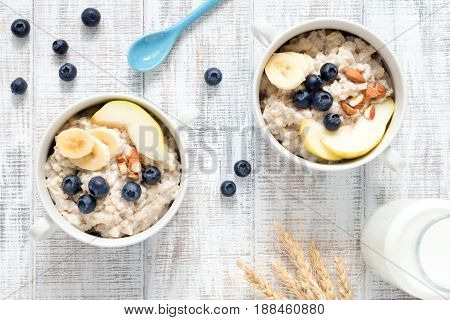 Two bowls of oatmeal porridge with blueberries, pear, banana and almonds on rustic white table background. Table top view