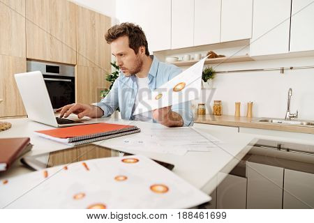 Working hard. Diligent serious man sitting in the kitchen, typing in the information with one hand while holding a sheet of paper in the other