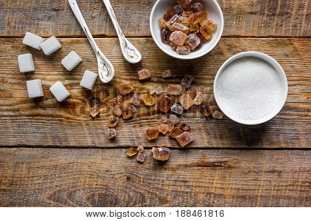 lumps of white and brown sugar on gray wooden table background top view mock up