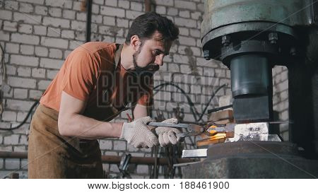 Man blacksmith in workshop forging red hot iron on anvil - small business, telephoto