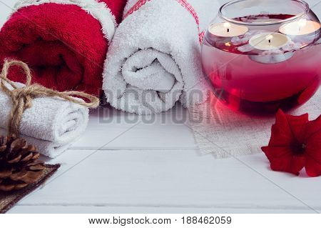 SPA consist from towels, candles, flowers, and aromatherapy water in a glass bowl on a white wooden background with empty space