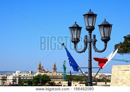 Maltese and EU flags on a lamppost with city buildings to the rear Valletta Malta Europe.
