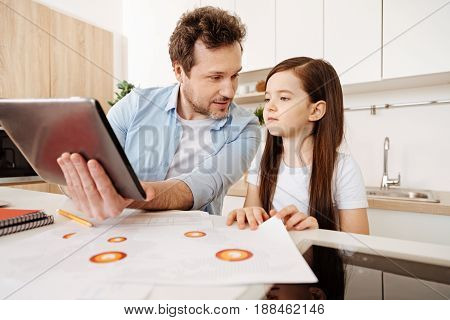 Loving look. Pleasant young father bonding to his daughter by showing her something on a tablet while looking at her with love and the daughter looking intently at the device.
