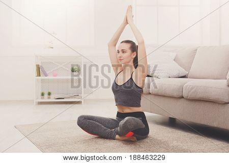 Yoga at home, woman do lotus pose, Padmasana asana. Young girl exercise