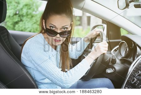Young Woman Looking At Camera While Driving A Car