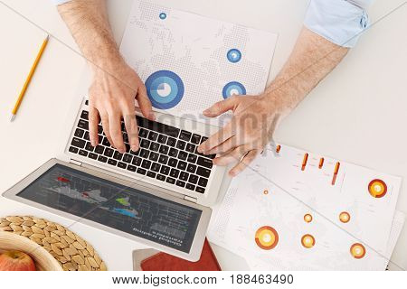 Neat workplace. Strong hairy male hands lying on the keyboard of a laptop standing on the white surface among printouts with diagrams, a fruit bowl and notebooks