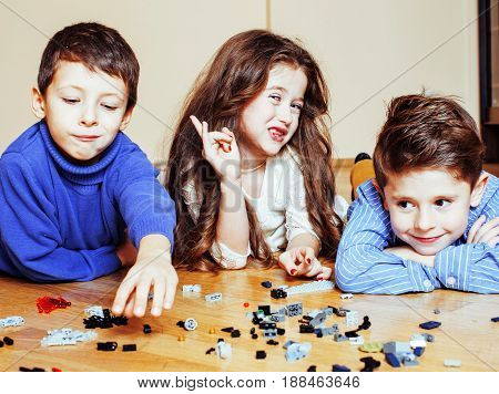 funny cute children playing toys at home, boys and girl smiling, first education role close up, lifestyle people concept close up