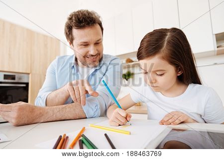 Love your drawing. Happy loving father looking at the picture of his little daughter, smiling and pointing at it with finger while she being involved into the creative process.